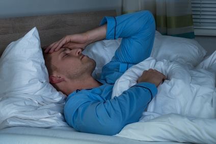 Man with his hand on his head having trouble sleeping from pain