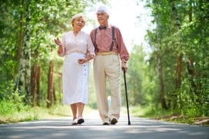 Elderly man and woman walking with cane in park
