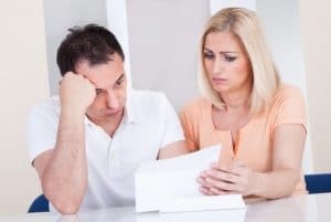 A couple reviewing paperwork looking stressed