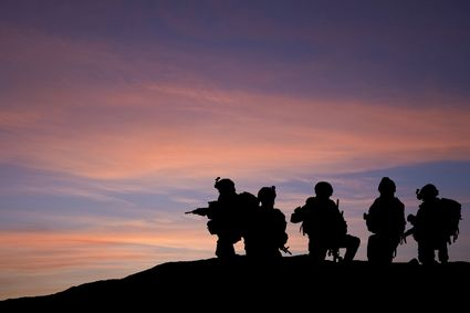 Modern troops silhouette against sunset sky in Middle East