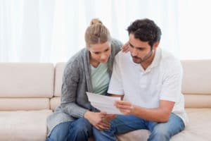 A couple sitting on a couch looking at a piece of a paper