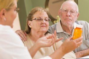 Doctor explaining medication prescription to senior couple