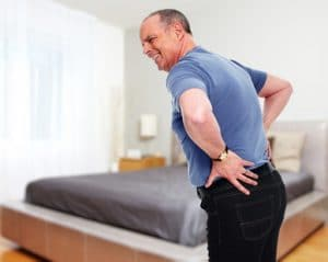 Senior man with back pain at home