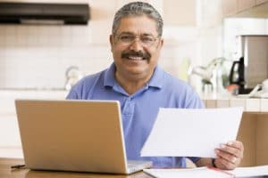 Man in front of a computer holding a piece of paper smiling
