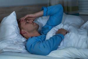 Man suffering from headache lying in bed in dark room