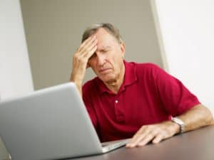 Senior man using laptop computer with headache and eyes closed
