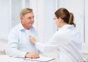 Female doctor listening to heart beat of elderly man