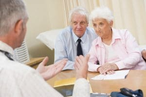 Concerned senior couple frowning while speaking to doctor