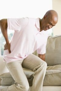Man getting off couch with back pain